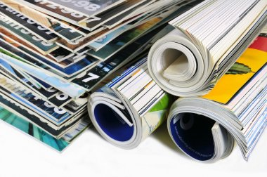 Stacked and rolled up magazines over white background