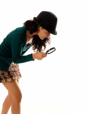Young woman with magnifier glass and hat looking for something isolated on