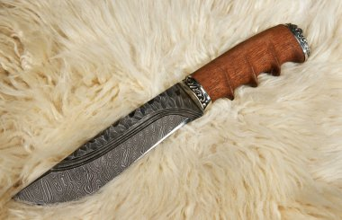 The hunting knife on a skin of a ram