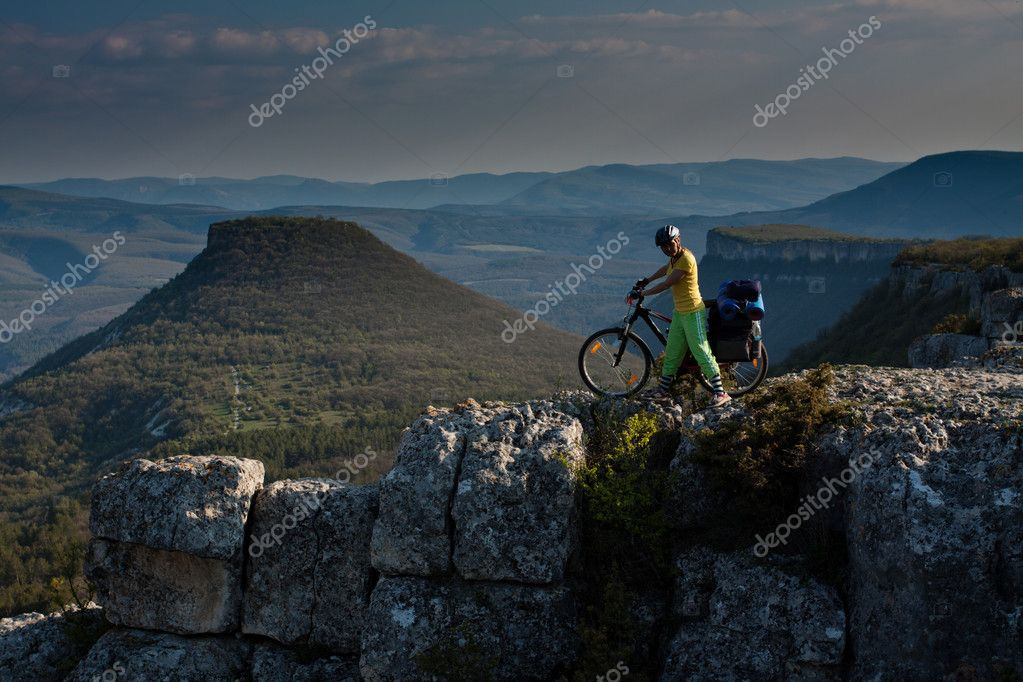Girl with bike in mountains.