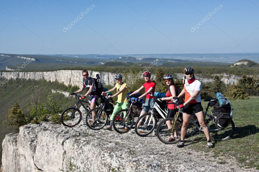 A group of five adults on bicycles in the countryside.