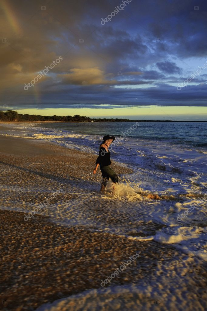 Woman walking on the shore alone