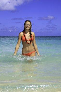 Girl in red bikini walking out of the ocean