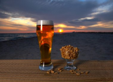 Fresh glass of pils beer with froth and condensed water pearls &