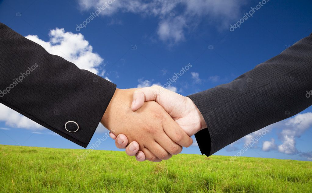 Business shaking hands against blue sky and green