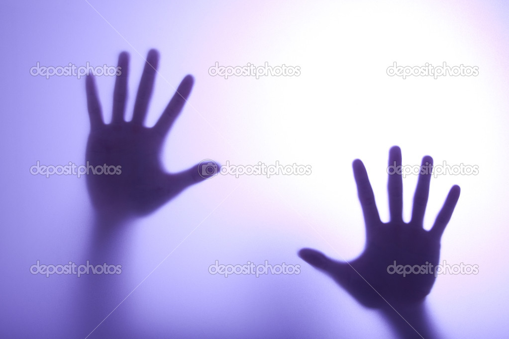 Blurry hands reaching out and touching glass with Blue light