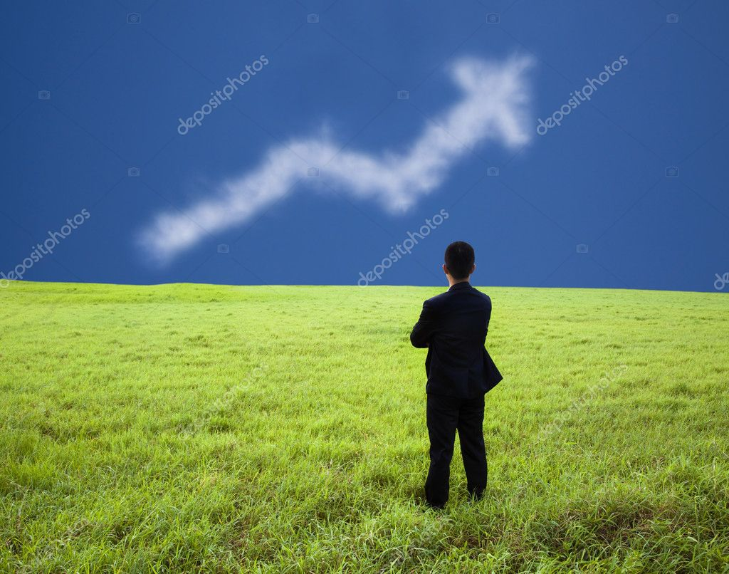 Businessman stand in the meadow and watch the business profit graph of clo