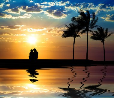 The silhouette of couple watching sunset on the beach