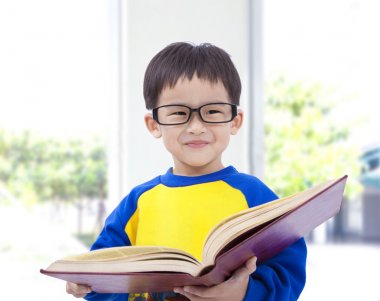 Asian kid smiling and holding book
