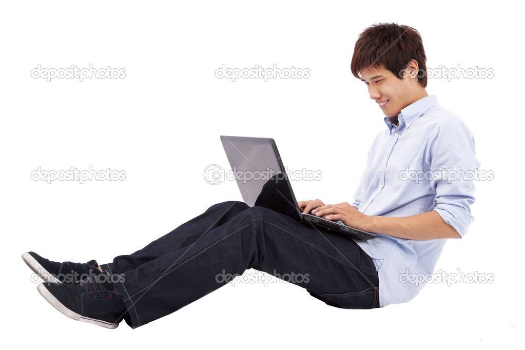 Happy and relax young man using laptop on the floor isolated on white backg