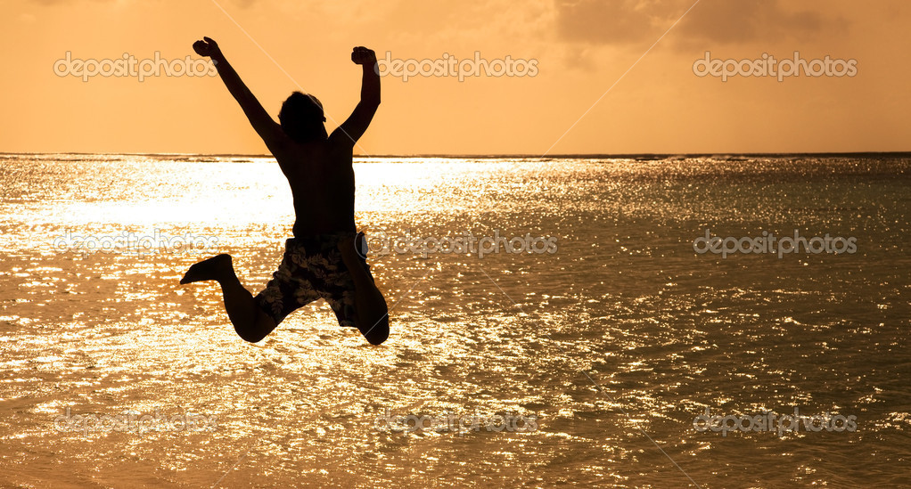 Happy Young man jumping on the beach at sunset