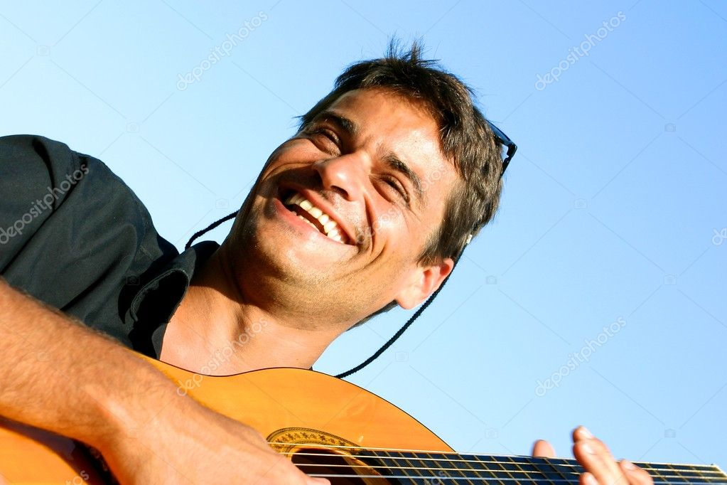 Cute young man playing guitar and smiling