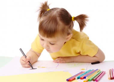 Cute child draws with felt-tip pens