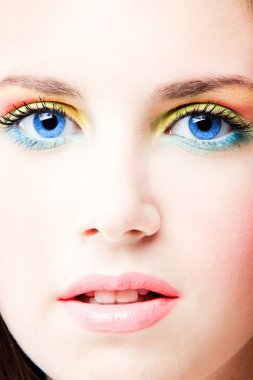 Young blue eyes woman close up face with colorful make up, studio shot stock vector