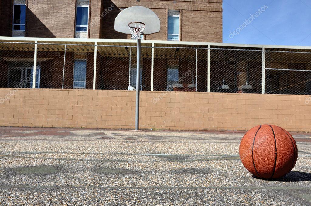 Outdoor basketball court in schoolyard.