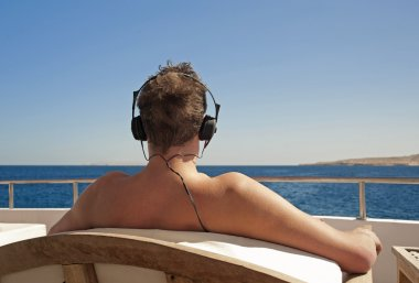 Person relaxing on a boat with headphones