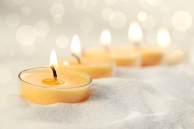 Votive candles in sand lit and arranged for ambiance stock vector