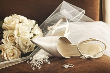 Wedding shoes with bouquet of white roses and ring