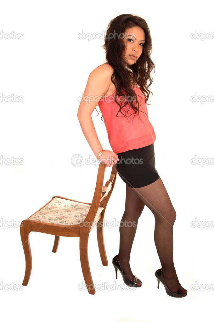 b64fc47d31 A young pretty Asian woman standing in the studio with her long brunette  hair and a short skirt and heels