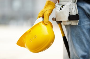 Builder with yellow helmet and working gloves on building site stock vector