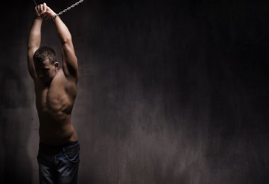 Young male model well build with chains over his arms