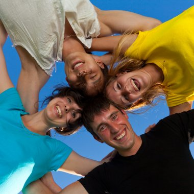 Below view of joyful teens embracing and looking at camera with