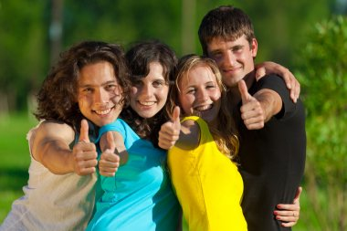 Young group of happy friends showing thumbs up sign