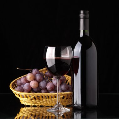 A bottle of red wine, glass and grapes