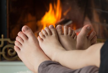 Children's feet are heated by an open fire in the fireplace