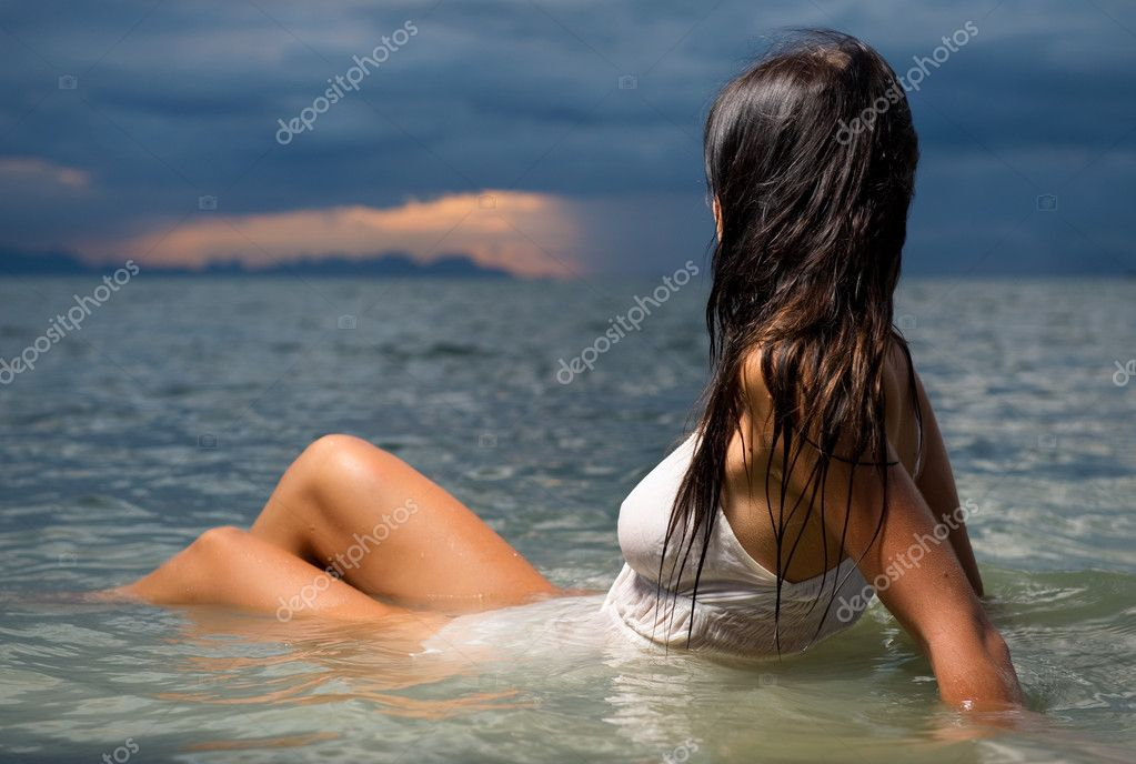 Beautiful brunette in the water at sunset
