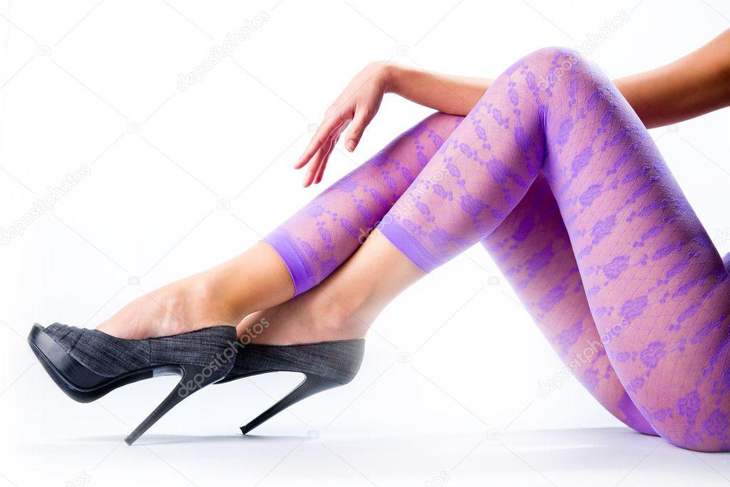 Female legs in purple leggings and high heels