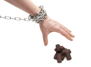 Woman's hand in chains reaching for candy