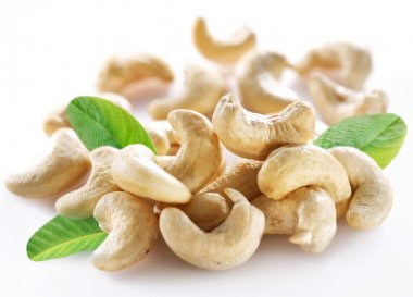 Ripe cashew nuts with leaves on a white background.