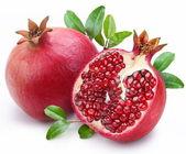 Fotografie šťavnaté granátové jablko a jeho polovinu s listy