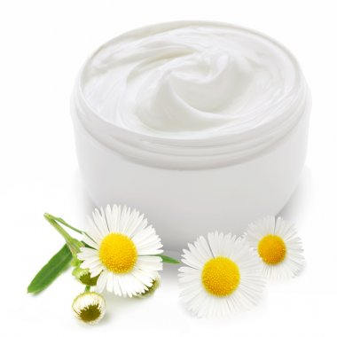 Opened plastic container with cream and camomile.