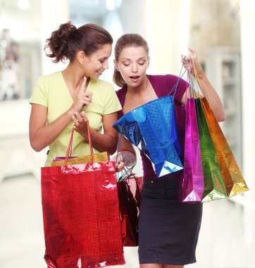 Two friends with shopping. One girl wonders purchases second gir