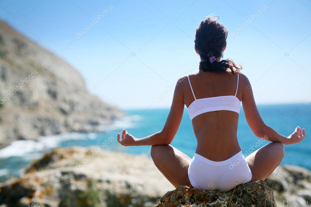 Woman meditating on a rocky seashore