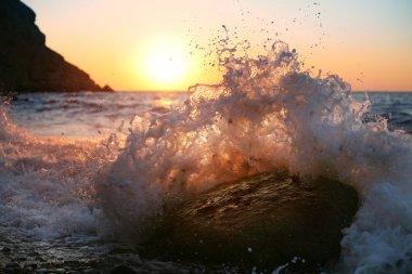 At sunrise, waves crash on the stone