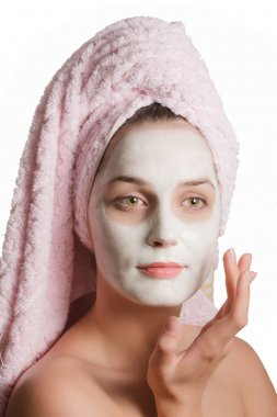 Beautiful girl in a rejuvenating mask with towel