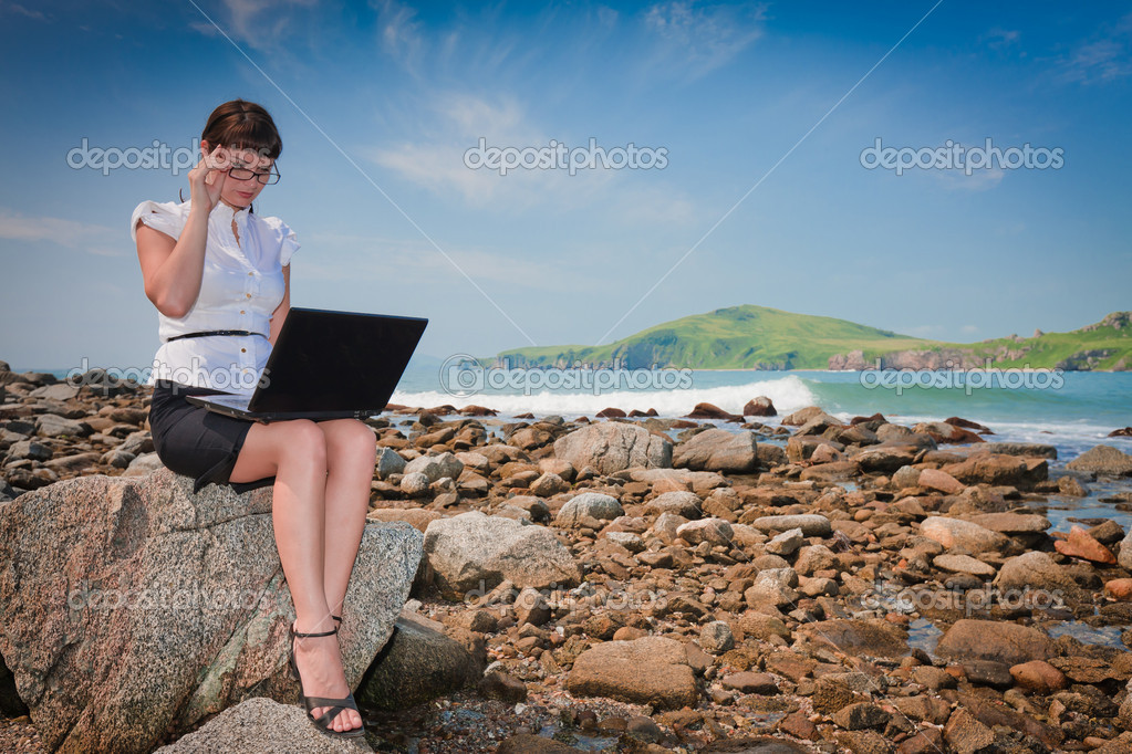 Successful girl on the beach with a laptop sitting