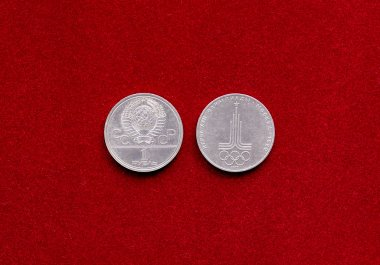 Old soviet ruble coin with symbol of 22 Olympic Game on red velvety backgr