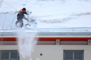 Man is de-icing a snowy Roof