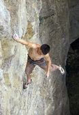 Photo Free climber holding on the cliff, view from above