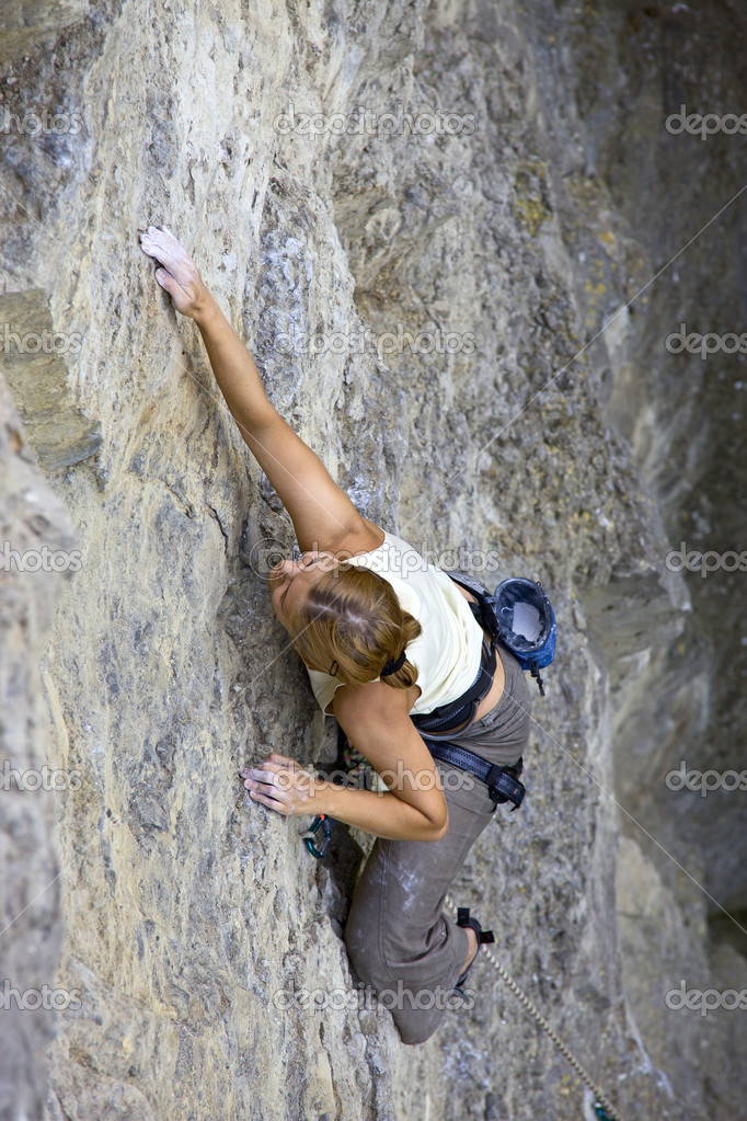 Female rock climber clinging to a cliff as she battles her way up
