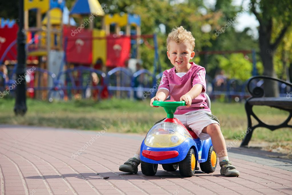 Preschooler driving his toy vehicle in the park