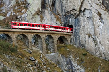 Train on an old bridge is going into a tunnel in mountains