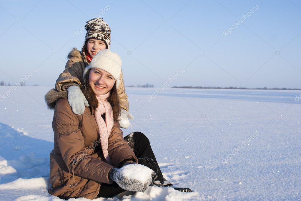 Teen girls sitting in snow