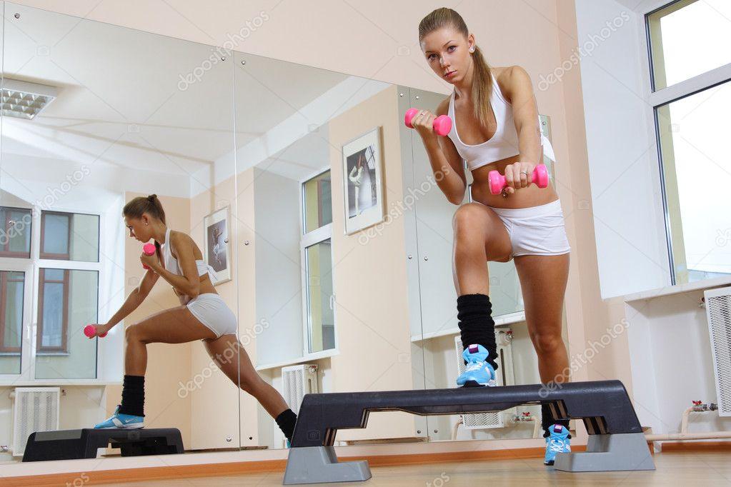 Girl on step hold dumbbells in fitness gym