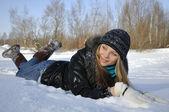 roztomilá dívka leží na sněhu v parku