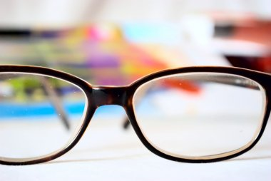 Glasses lie on a table against the background of bright magazine